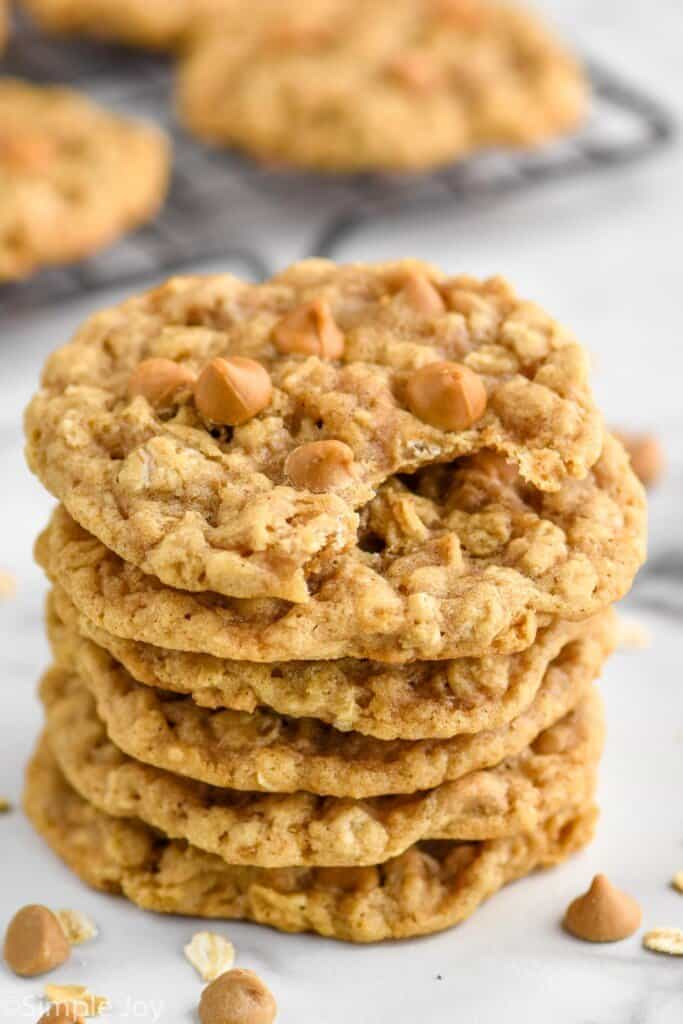 a pile of oatmeal butterscotch cookies with a bite taken out of the top one