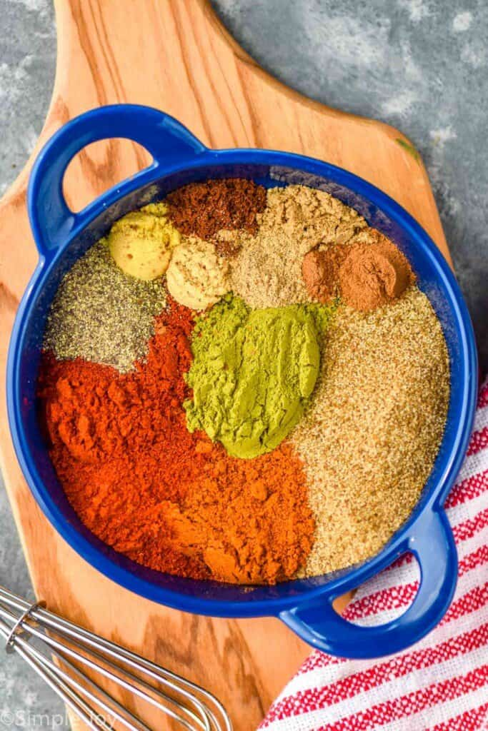 overhead of a small blue dish with old bay seasoning ingredients separated by spice