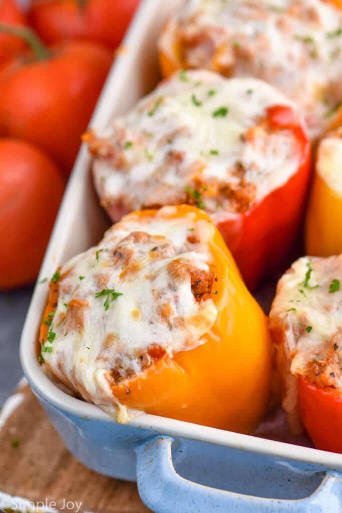 close up of an orange stuffed bell pepper in a baking dish