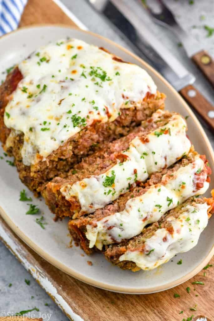 an italian meatloaf sliced and on a serving dish topped with melted cheese and fresh parsley