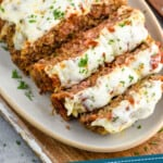 pinterest graphic of an italian meatloaf sliced and on a serving dish topped with melted cheese and fresh parsley