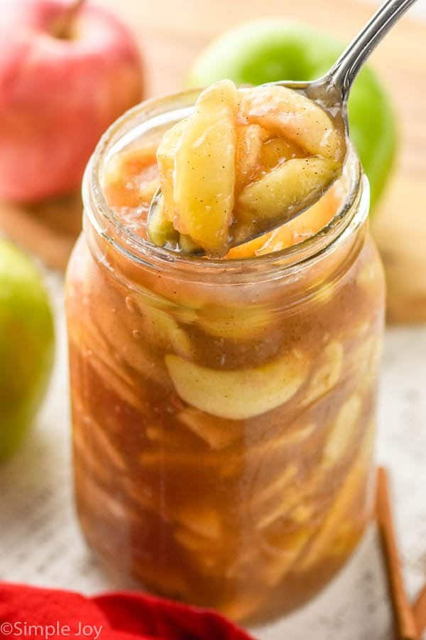 apple pie filling being spooned out of a large mason jar
