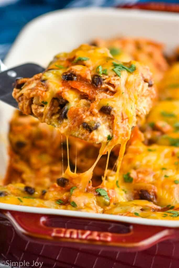 a piece of chicken enchilada casserole being dished out of a baking dish