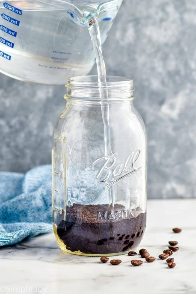 pouring water into a mason jar that has coffee grounds in it
