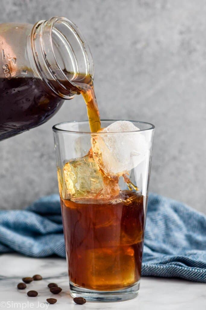 pouring a cold brew recipe over a ice in a glass tumbler