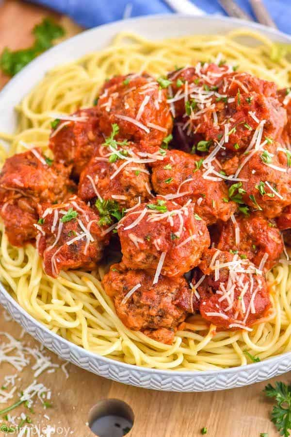 a crockpot meatball recipe on top of spaghetti