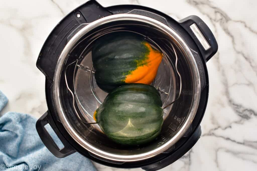 overhead picture of an acorn squash that has been cut in half inside of a pressure cooker