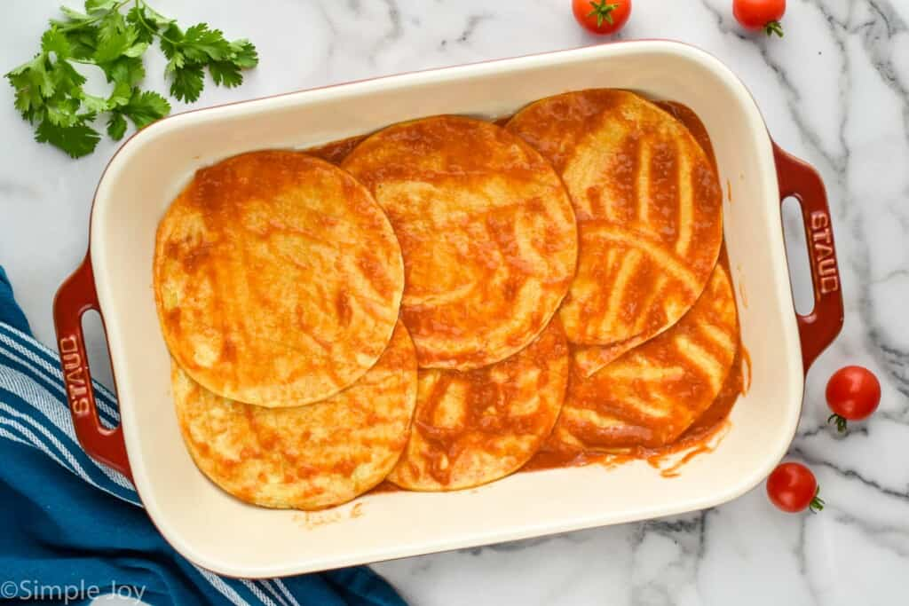 overhead of a baking dish showing six corn tortillas coated in enchilada sauce in a bottom layer