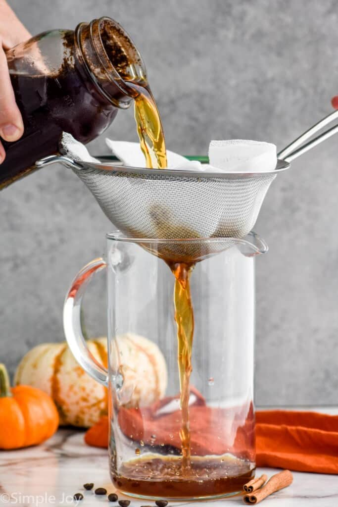 straining pumpkin cold brew with a metal strainer and a cheesecloth into a pitcher