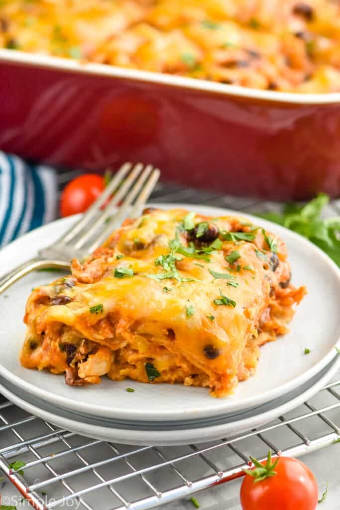 a pice of layered chicken enchilada casserole on a plate