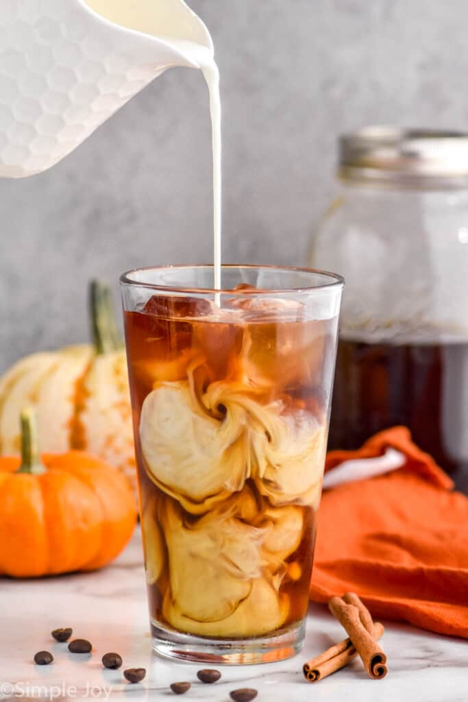 cream being poured into pumpkin cold brew