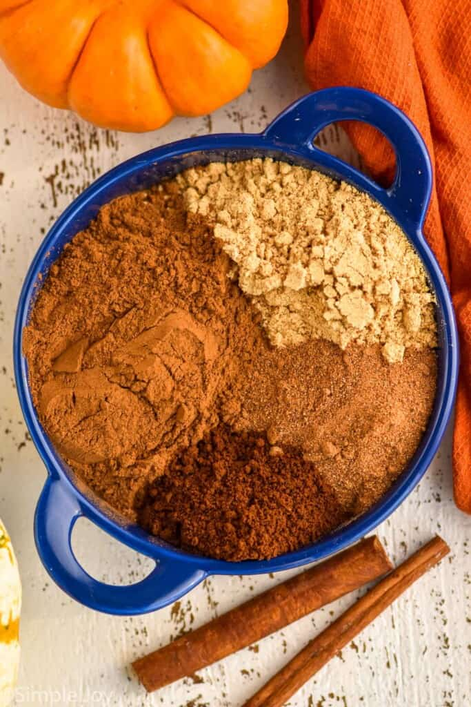 overhead of a small blue dish with the four different spices that make up pumpkin pie spice