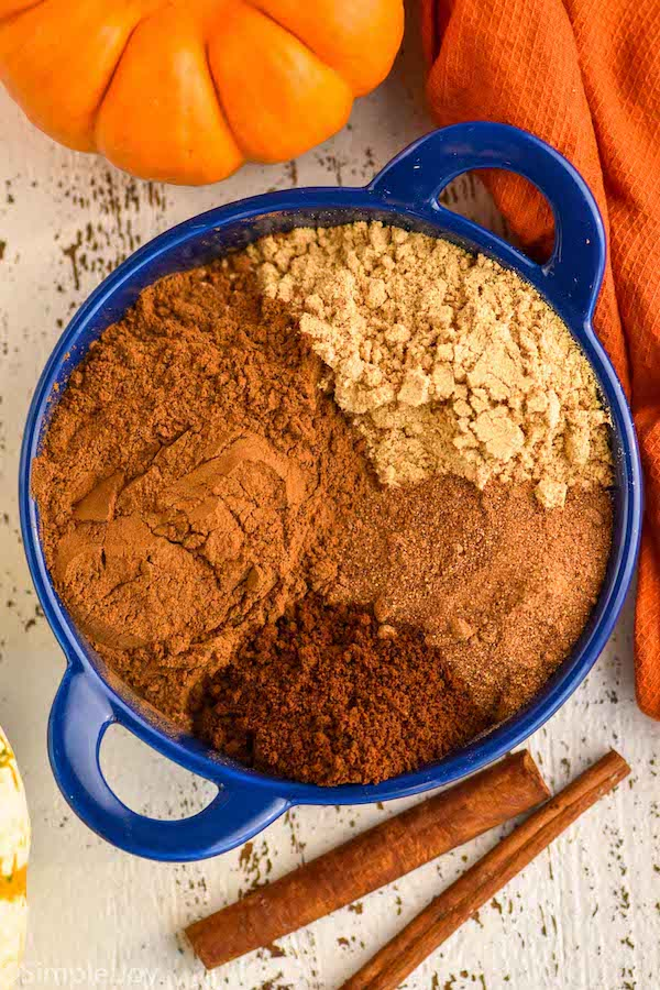 pinterest graphic of overhead of a small blue dish with the four different spices that make up pumpkin pie spice
