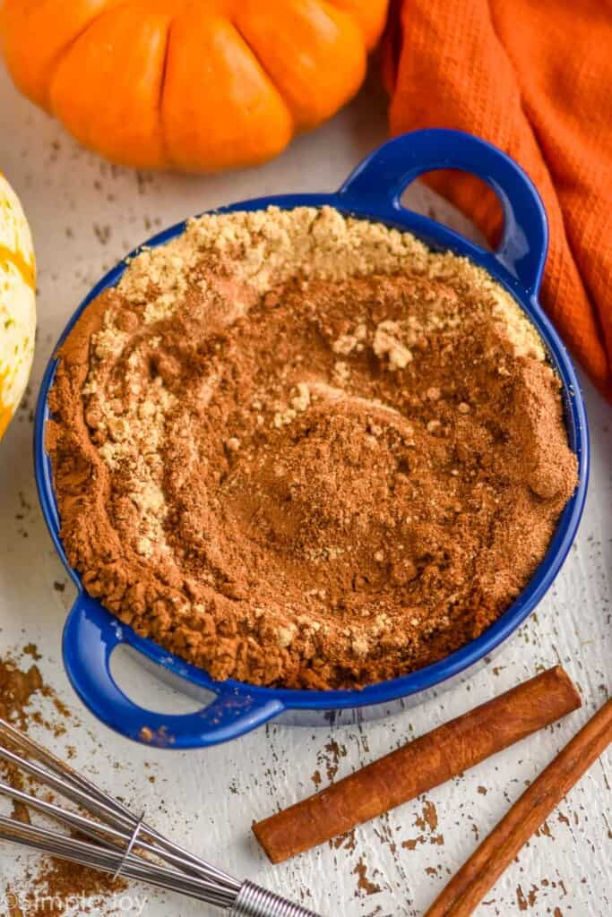 small blue dish with a mixture of spices that make pumpkin pie spice substitute