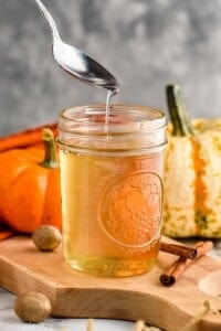 a spoon dripping pumpkin spice syrup into a mason jar full of it