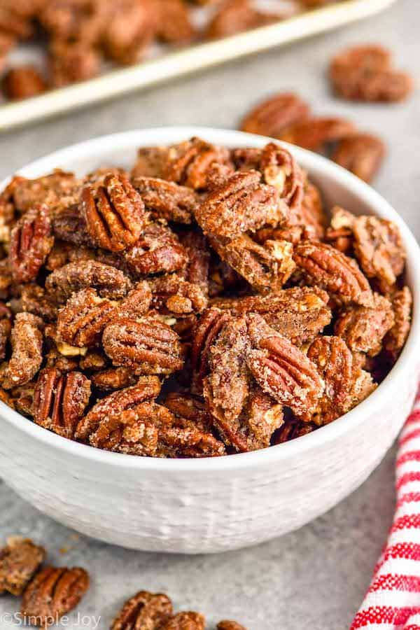 pinterest graphic of small white bowl full of candied pecans