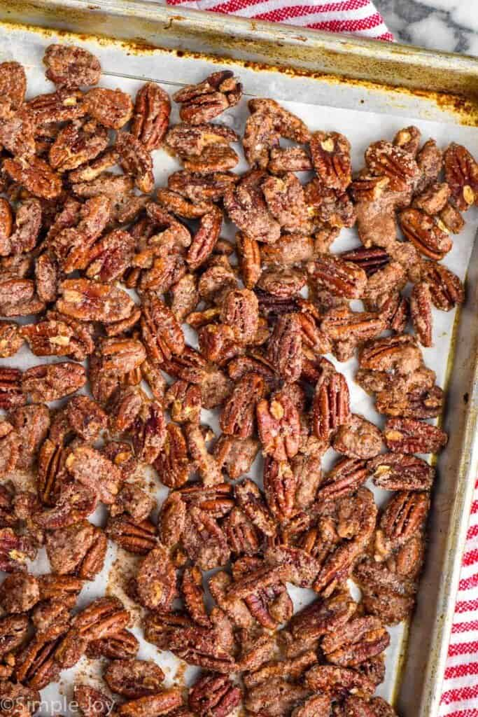 overhead of a rimmed baking sheet with candied pecan recipe