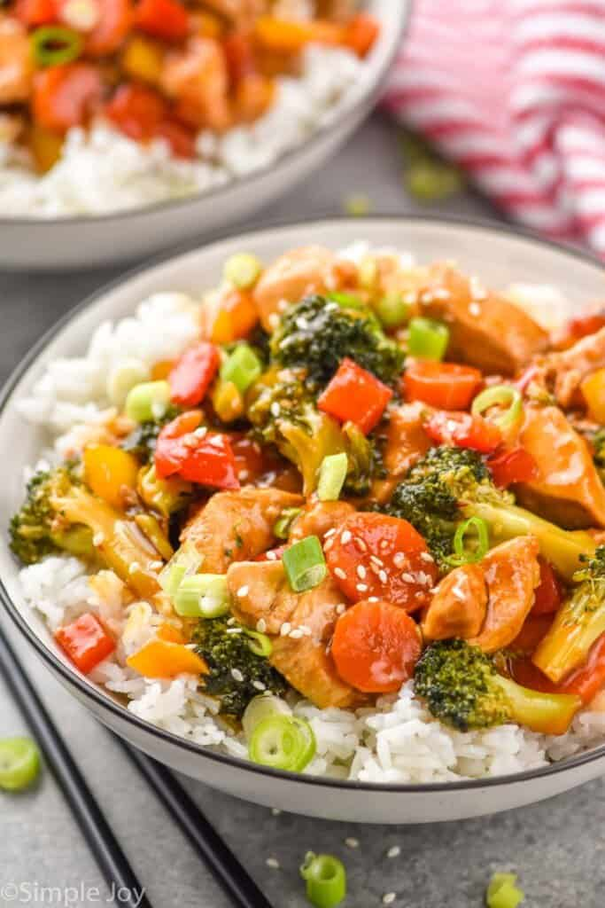 a bowl of rice with chicken and broccoli stir fry on top
