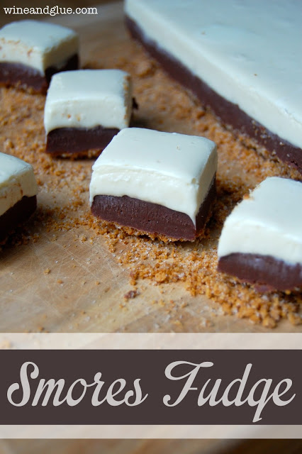 S'mores Fudge with a graham cracker crust and delicious marshmallow fudge topping sandwiching a delicious chocolate fudge!